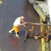 havenwerk duwt bok onder een trailer aan boord van een roro schip